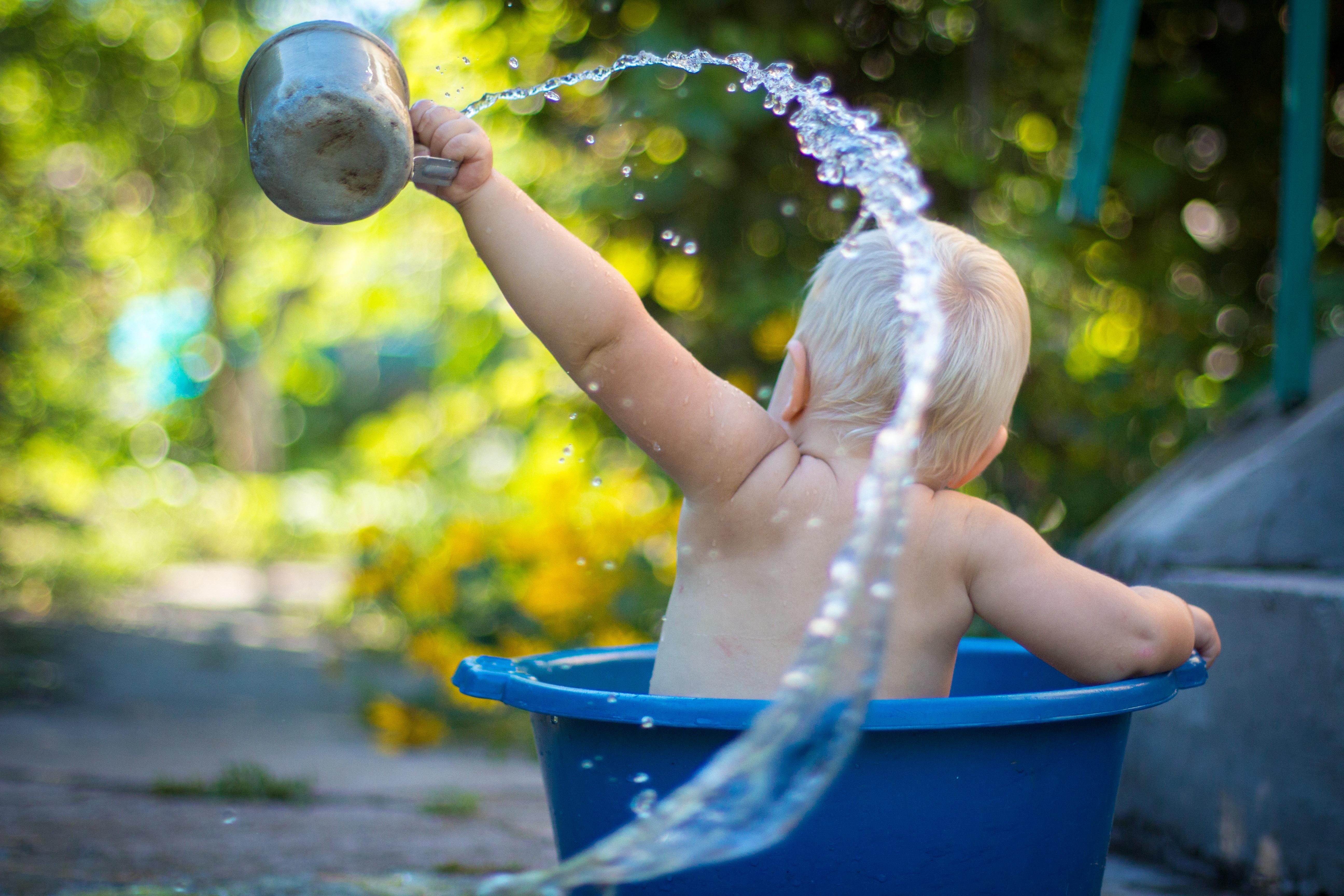 Bambin dans une bassine qui lance de l'eau
