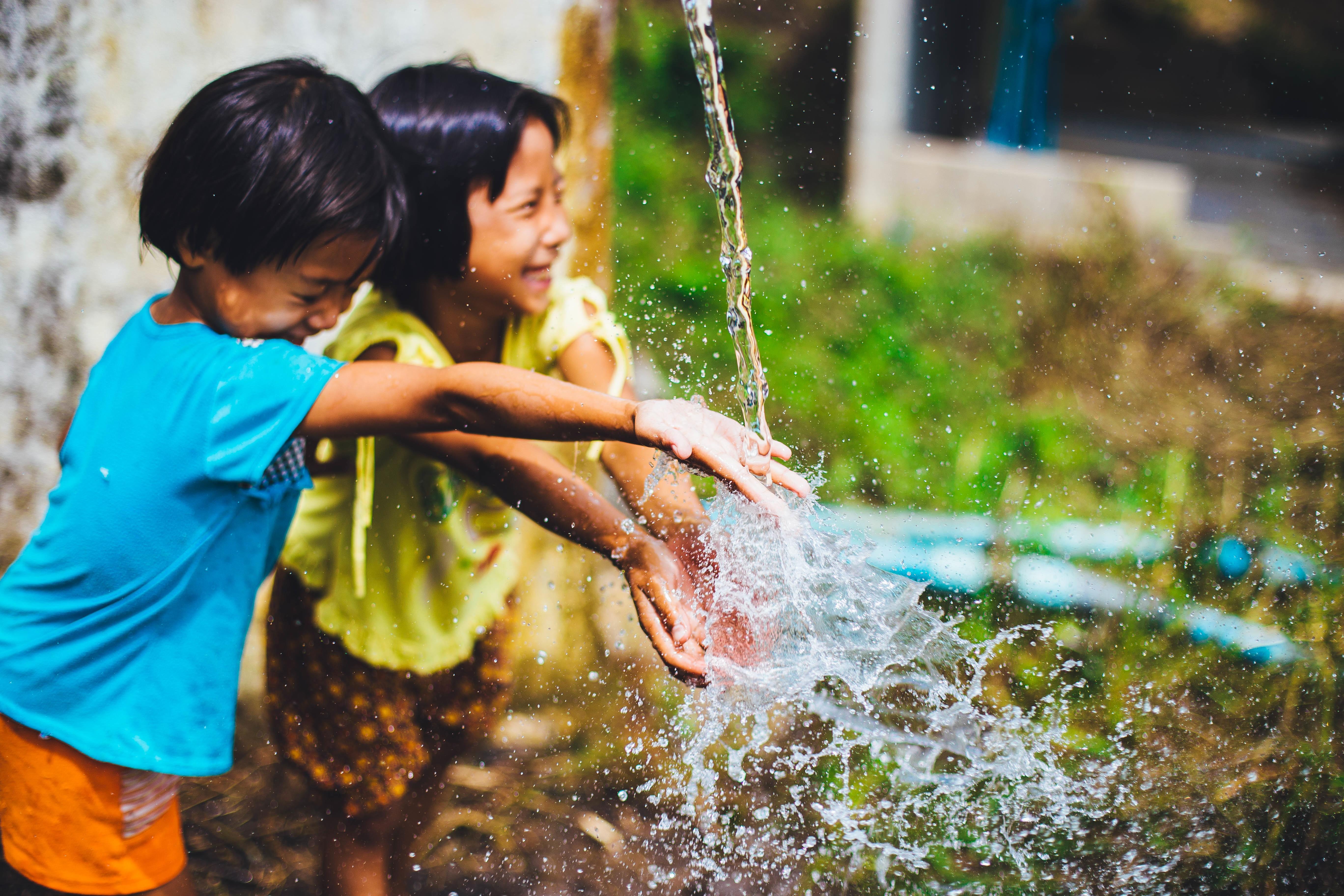 Enfants jouant avec un jet d'eau